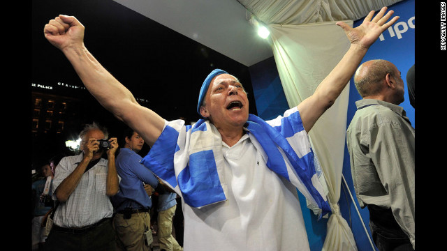 A New Democracy supporter celebrates as he watches the exit polls at the party's election campaign kisok in Athens.