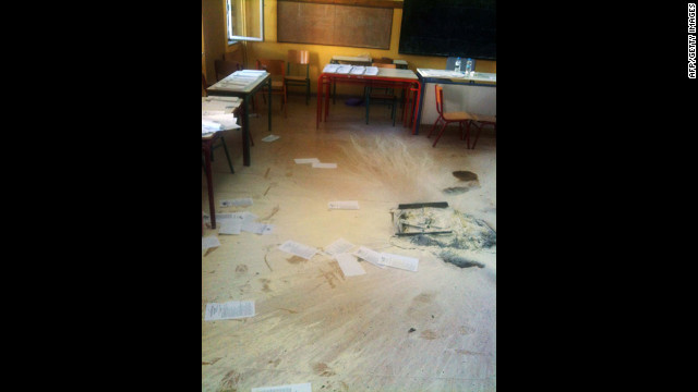 The ashes of a burned ballot box remain on the floor at a polling station in central Athens. A masked group stormed the room and lit the box full of ballots on fire just before the end of voting on Sunday.