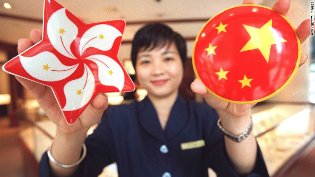 A shop assistant for luxury jeweler Tiffany's displays two porcelain souvenir boxes for sale, one featuring the new Bauhinia flower emblem of Hong Kong, the other the five stars of the Chinese flag.