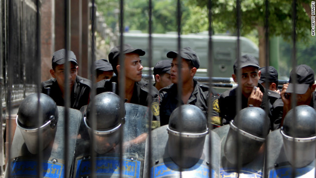 Egyptian riot police stand outside parliament as protesters gather in Cairo on Tuesday.