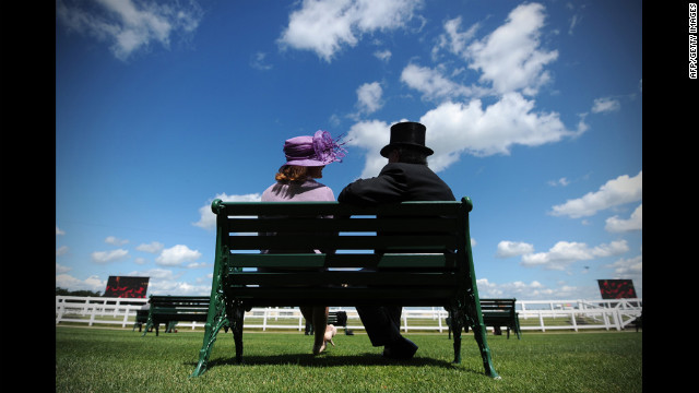 Race-goers sit together on a bench.