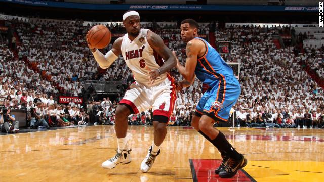 LeBron James of the Miami Heat drives to the basket against Thabo Sefolosha of the Oklahoma City Thunder.