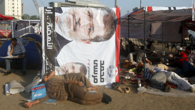 Egyptian activists rest at the foot of a banner of presidential candidate Mohamed Morsi in Cairo's Tahrir Square on Thursday, June 21. 