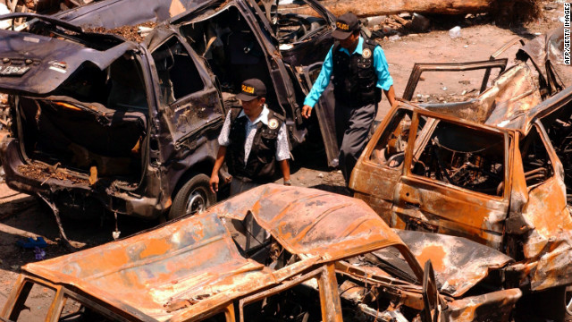 "Indonesian police investigators walk through the wreckage of cars left twisted and burnt after the bomb attack in Bali. One witness, Nicolle Haigh, told police: ""I've been told that there was about 45 seconds between explosions, but it felt like 10 seconds. One moment I was talking to friends, and the next was like being in a war zone."""