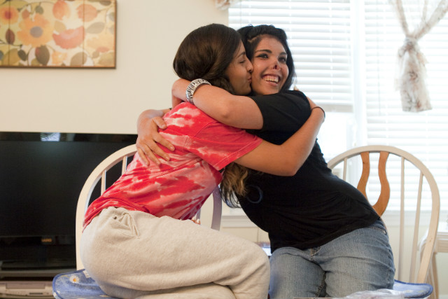 Aesha, right, hugs Miena, a high school student and athlete who has become a sister to her.