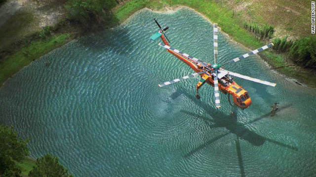 This is Greer's award-winning image of an Erickson Air-Crane dipping into a pond to fill its tank on the Oakhead Complex Fire in Osceola National Forest, Florida. The image won first place in the &quot;aerial resources&quot; category of a Fire &amp;amp; Aviation Management photo contest in 2004.