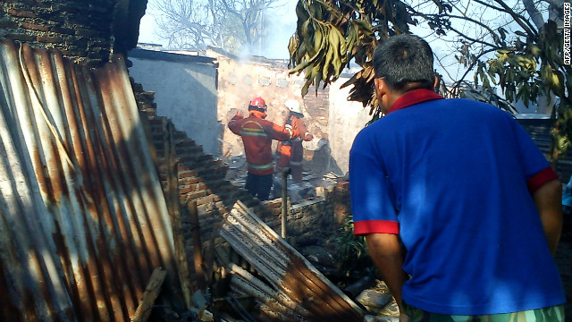 Emergency personnel look through a damaged building after an Indonesian military aircraft crashed in Jakarta on Monday.