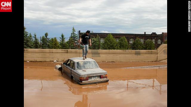 Ian Koivisto drove his car into this flooded area of Dultuh, Minnesota, early Thursday and then had to swim to safety. Richard Thomas, a CNN iReporter, took this photo of Koivisto atop his car.