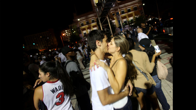 A couple kisses as Miami Heat fans celebrate the Heat's victory over the Oklahoma City Thunder in the 2012 NBA Finals in Miami.
