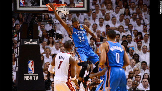 Kevin Durant, No. 35 of the Thunder, hangs on the rim after a dunk in the first half against the Heat. View photos from Game four of the NBA Finals.