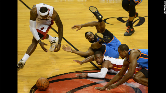 LeBron James, left, and the fallen Dwyane Wade, center, of the Heat go for the ball before the tumbled James Harden, center top, and Serge Ibaka, right, of the Thunder.