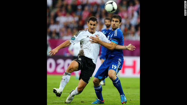 Miroslav Klose of Germany and Sokratis Papastathopoulos of Greece fight for the ball.