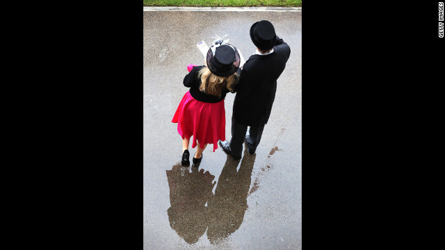 A couple stand in a puddle at Royal Ascot.