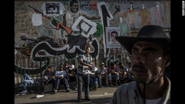 Protesters gather in front of wall art in Tahrir Square.