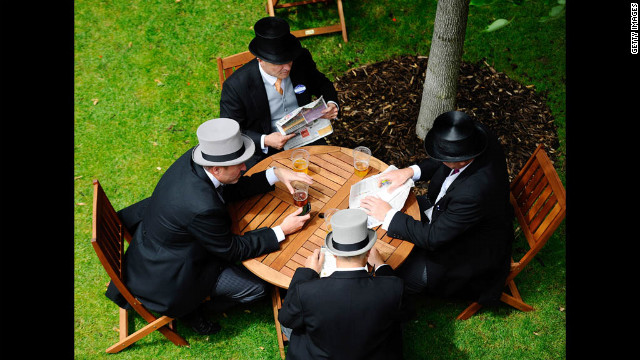 Racegoers sit at a table and study the form on Friday.