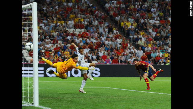 Xabi Alonso of Spain scores the first goal past Hugo Lloris of France.