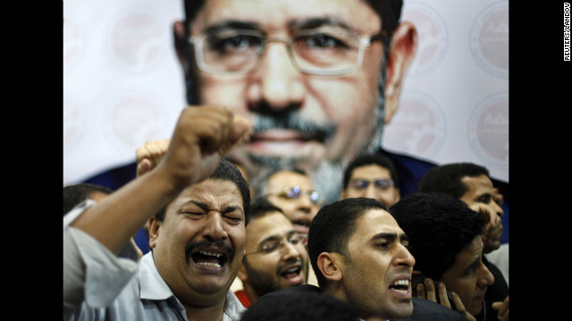 Morsi suppporters celebrate in front of a picture of him at his campaign headquarters in Cairo on June 24.