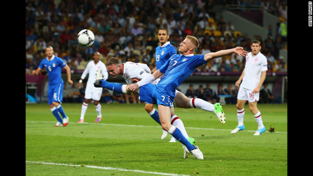 Wayne Rooney of England heads the ball as Ignazio Abate of Italy challenges during the quarterfinal match.