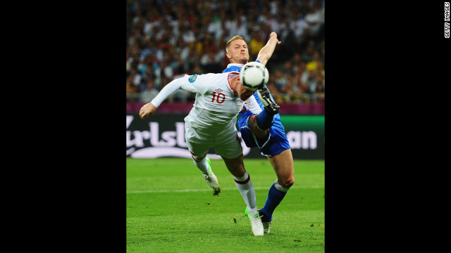 Wayne Rooney of England and Ignazio Abate of Italy go after the ball.