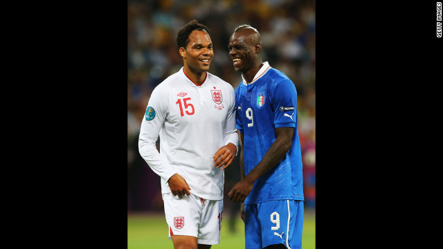 Joleon Lescott of England and Mario Balotelli of Italy share a moment during a break in the match.