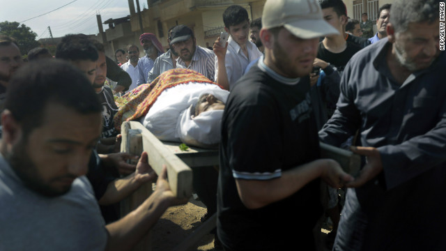Syrian mourners carry the body of a victim of the previous day's shelling on the rebel stronghold of Qusayr on Saturday.