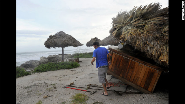 Jeff Higgins, manager of the Gulf Drive Cafe, inspects damage to his restaurant Monday as high winds associated with Debby batter Bradenton Beach, Florida.