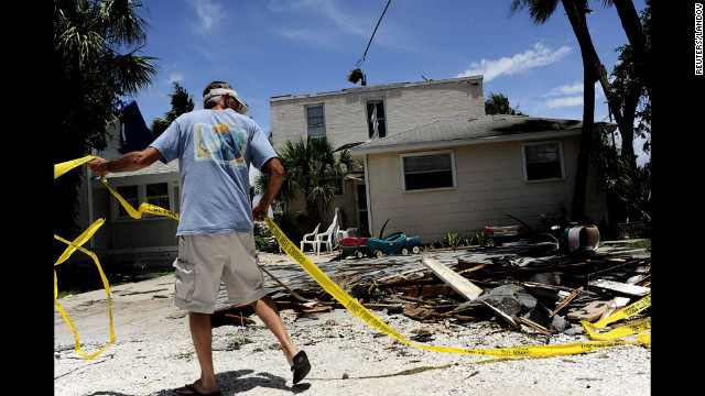 Mike Foster uses caution tape Monday to rope off what's left of a roof on his employer's property after the storm hit Pass-A-Grille Beach, Florida.