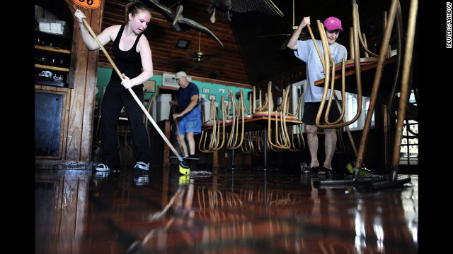 Brittany Cheak, from left, Al Church and Angie Cheak help mop up inside the Seahorse Tavern &amp; Restaurant on Monday in St. Pete Beach, Florida.