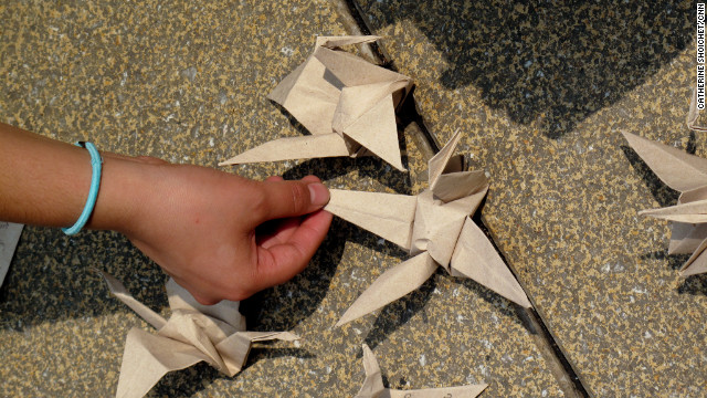An activist in Mexico City places an origami bird on a sidewalk as part of an art project to promote peace.