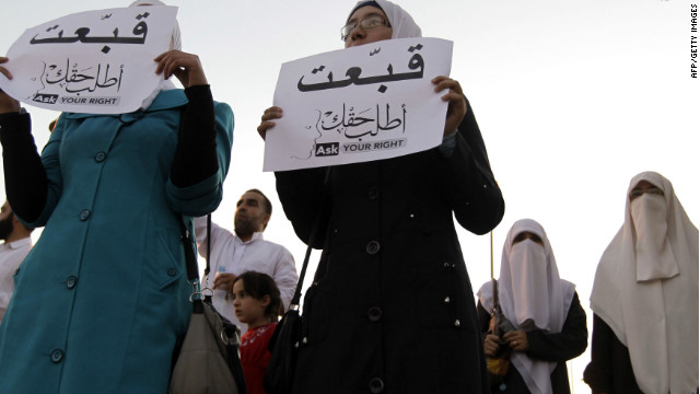 Jordanian women hold up signs that say