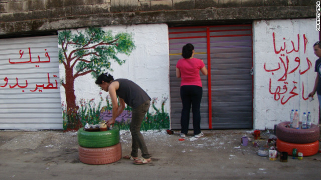 Layla Serhan and another YNCA member paint a mural in Nabatieh. The group aims to empower the town's young people, traumatized by the 2006 conflict with Israel, to voice their opinion; it spreads its message through art.