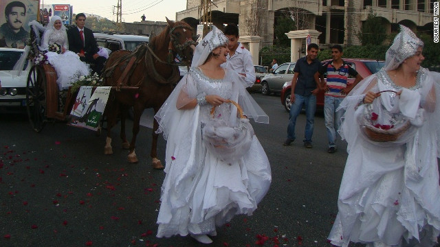 Women dance in the street before a carriage bearing newlyweds affiliated with YNCA. The organization used the occasion to declare a &quot;week of joy,&quot; and encouraged people to celebrate by dancing in the street, defying prohibitions against such behavior that have arisen in recent years.