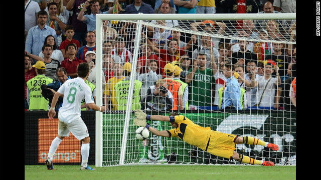 Spanish goalkeeper Iker Casillas stops a penalty kicked by Portuguese midfielder Joao Moutinho.