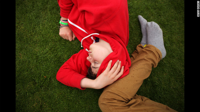Tournament-goers relax in the grass Wednesday.