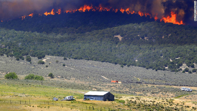 A wall of fire makes its way down a hillside toward a farm north of Fairview, Utah, on Tuesday. The Wood Hollow Fire, one of at least three wildfires burning in Utah, has grown to nearly 39,000 acres.