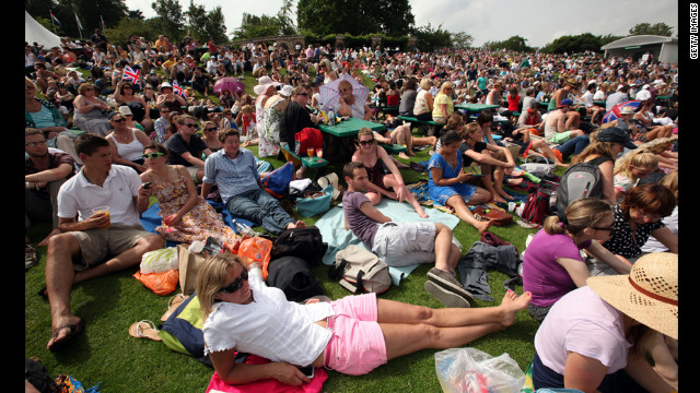 Fans watch the men's singles second-round match between Andy Murray of Great Britain and Ivo Karlovic of Croatia on a large projection screen from the lawn June 28.