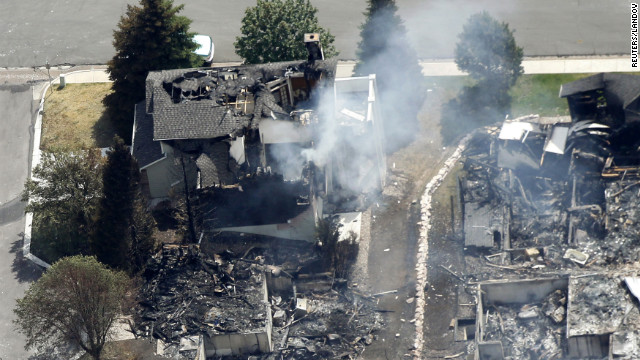 A partially burned home<br /> 1000<br />  smolders Thursday in Colorado Springs.