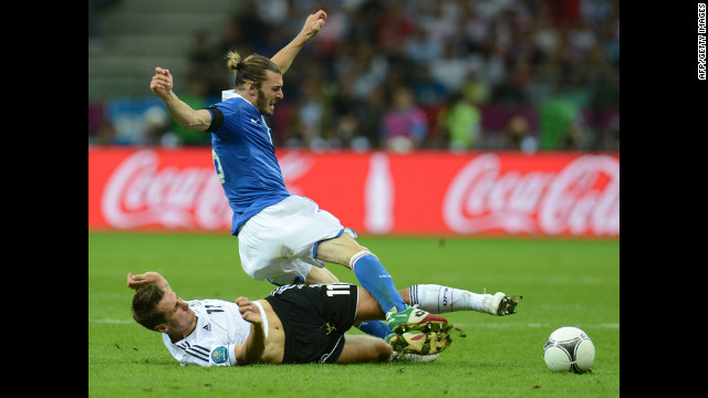 German forward Miroslav Klose lands on the ground while vying with Italian defender Federico Balzaretti.