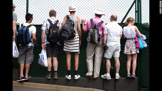 Fans peek through a fence to catch the action June 28 at Wimbledon.