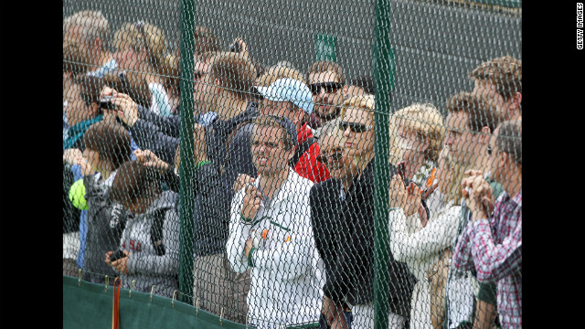 The crowd gathers and watches from behind a fence Friday.