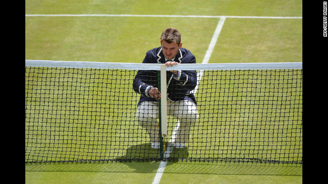 A umpire measures the height of the net on No. 2 Court on Friday.
