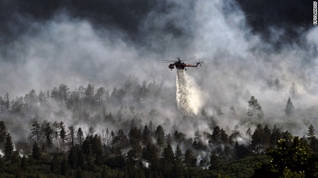 A helicopter drops water over the Waldo Canyon Fire northwest of Colorado Springs on June 27, 2012. The Western wildfires that devastated parts of Colorado, Idaho, Wyoming, Montana, California, Nevada, Oregon and Washington are expected to bring costs of about $1 billion.