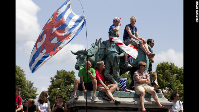 Cycling fans sit on a bronze statue in the town of Liege, Belgium, to get a glimpse of the individual time trial on Saturday.