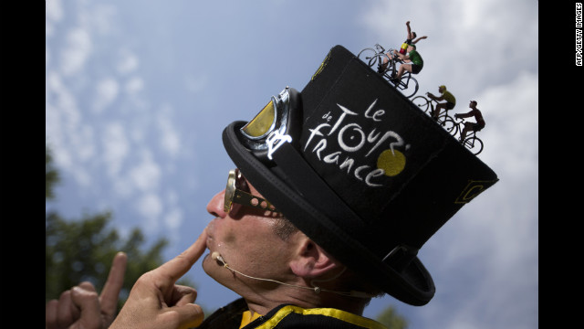 A performer wearing a hat decorated with toy cyclists poses for spectators on Saturday.