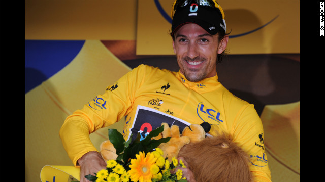 Cancellara celebrates on the podium Saturday and pulls on the yellow jersey, worn by the overall race leader.
