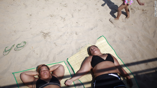 Beachgoers lie in the sun at Coney Island on Saturday.