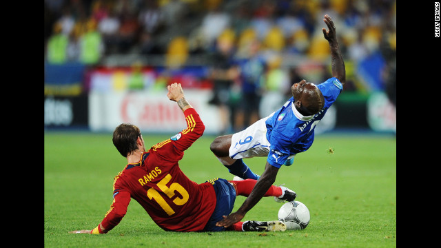 Spain's Sergio Ramos slides in to tackle Mario Balotelli of Italy.