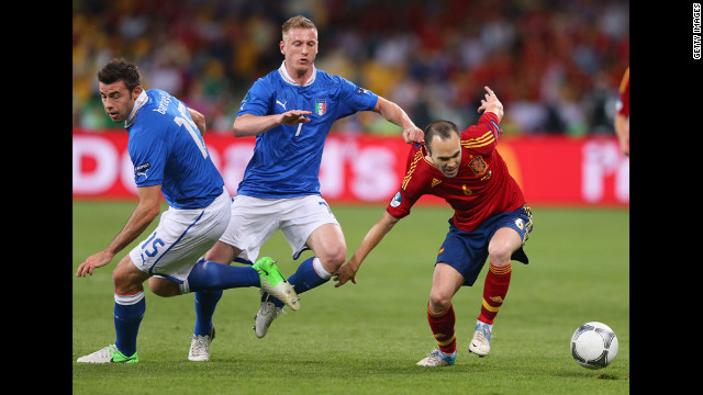 Ignazio Abate of Italy, center, grabs the shirt of Spain's Andres Iniesta.