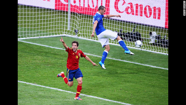 Jordi Alba of Spain celebrates after scoring his team's second goal as Leonardo Bonucci of Italy kicks the ball in frustration.