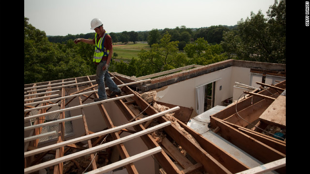 An employee of CRS Roofing walks across newly placed roof beams his company was hired to replace on the Park Tanglewood Apartments in Riverdale, Maryland.